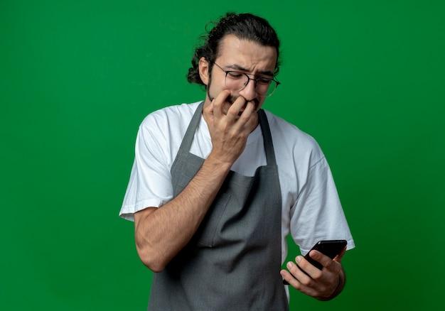 Angstige jonge kaukasische mannelijke kapper uniform en bril houden en kijken naar mobiele telefoon met hand op mond geïsoleerd op groene achtergrond met kopie ruimte
