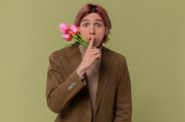 Angstige jonge knappe man die bloemen vasthoudt en een stiltegebaar doet