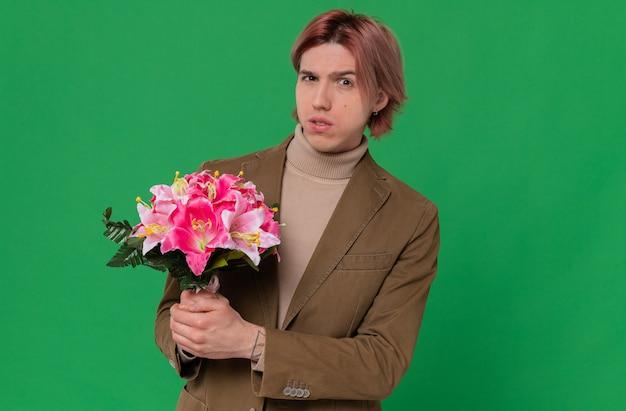 Angstige jonge knappe man die een boeket bloemen vasthoudt en kijkt