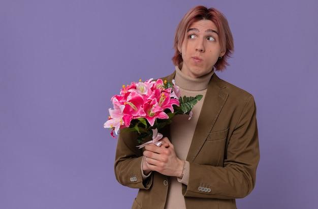 Angstige jonge knappe man die een boeket bloemen vasthoudt en naar de zijkant kijkt