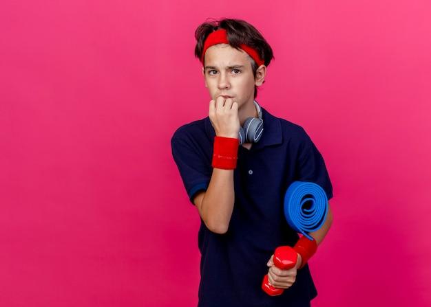 Angstige jonge knappe sportieve jongen die hoofdband en polsbandjes en koptelefoon op de nek draagt, halter met handdoek houdt, kin geïsoleerd raakt