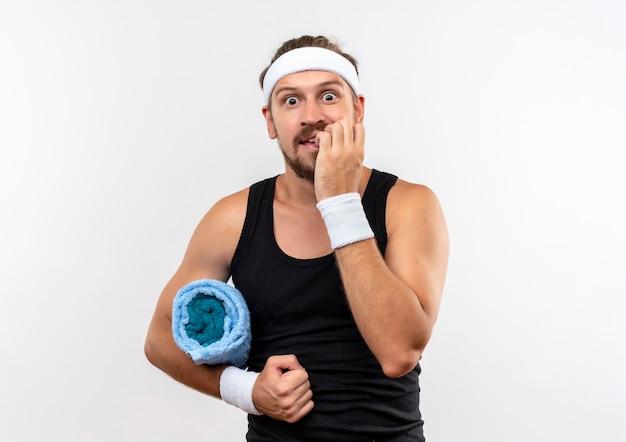 Angstige jonge knappe sportieve man met hoofdband en polsbandjes die een handdoek vasthouden en zijn vingers bijten geïsoleerd op een witte muur met kopieerruimte