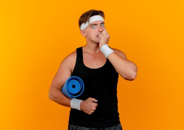 Angstige jonge knappe sportieve man met hoofdband en polsbandjes met handdoek en bijtende vingers geïsoleerd op oranje met kopie ruimte