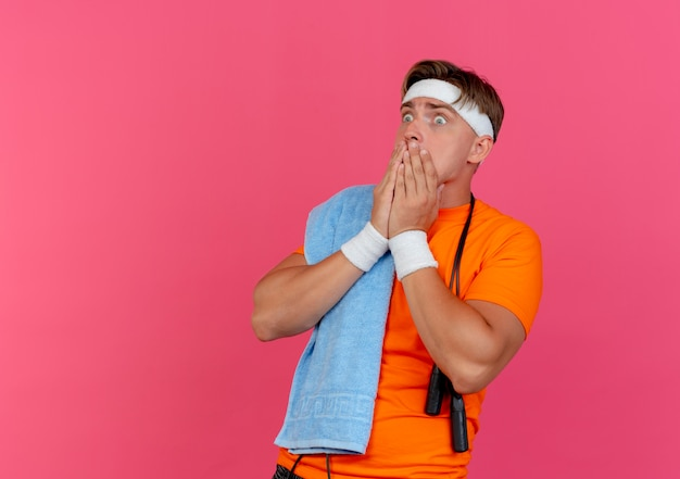 Angstige jonge knappe sportieve man met hoofdband en polsbandjes met handdoek en springtouw rond de nek op zoek recht handen op de mond geïsoleerd op roze met kopie ruimte