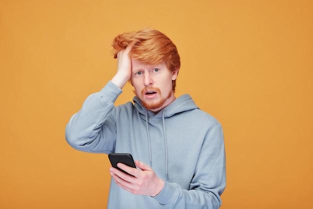 Angstige jonge man met rood haar hoofd aan te raken en naar de voorkant te kijken tegen de gele muur tijdens het lezen van het laatste nieuws in de mobiele telefoon