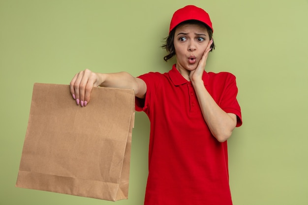 Angstige jonge, mooie bezorger die haar hand op haar gezicht legt en papieren voedselverpakkingen vasthoudt