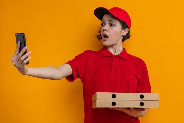 Angstige jonge mooie bezorger die pizzadozen vasthoudt en naar de telefoon kijkt