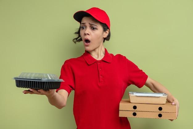 Angstige jonge, mooie bezorger die voedselverpakkingen op pizzadozen vasthoudt en naar voedselcontainers kijkt