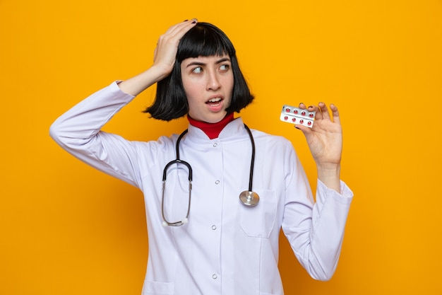 Angstige jonge, mooie blanke vrouw in doktersuniform met een stethoscoop die de hand op haar hoofd legt en een pillendoosje vasthoudt