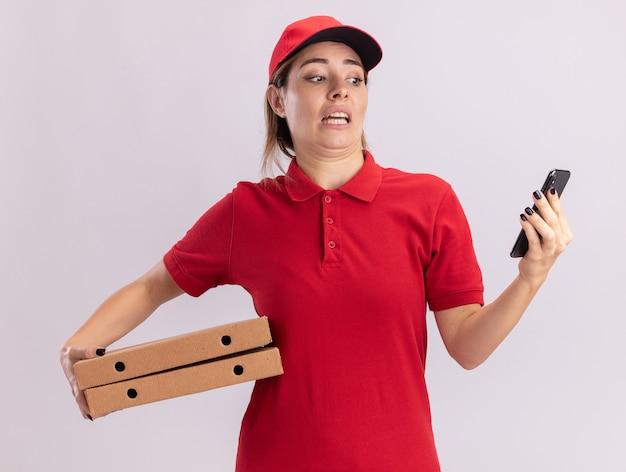 Angstige jonge mooie levering vrouw in uniform houdt pizzadozen en kijkt naar telefoon geïsoleerd