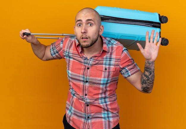 Angstige jonge reiziger man met koffer op zijn rug staande met opgeheven hand geïsoleerd op oranje muur met kopieerruimte