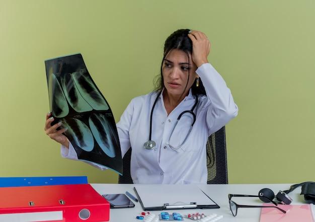 Angstige jonge vrouwelijke arts draagt ?? medische mantel en stethoscoop zit aan bureau met medische hulpmiddelen houden en kijken naar x-ray shot houden hand op hoofd geïsoleerd