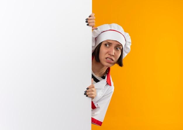 Angstige jonge vrouwelijke kok in eenvormige chef-kok die kant van achter witte muur bekijkt die op oranje met exemplaarruimte wordt geïsoleerd