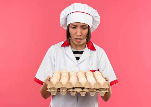 Angstige jonge vrouwelijke kok in uniform chef-kok houden en kijken naar doos eieren geïsoleerd op roze met kopie ruimte