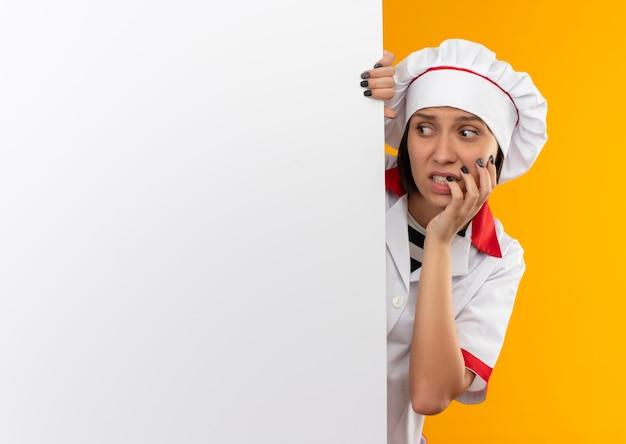 Angstige jonge vrouwelijke kok in uniform chef-kok staande achter de witte muur en kijken naar kant met hand op wang geïsoleerd op oranje met kopie ruimte