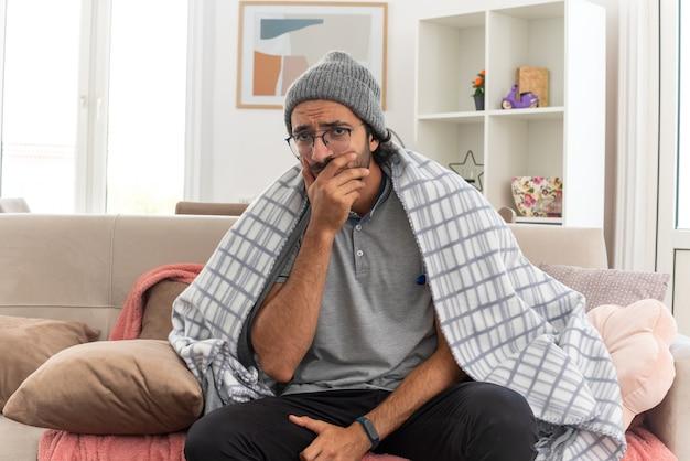 Angstige jonge zieke man in optische bril gewikkeld in een geruite muts met een wintermuts die zijn temperatuur meet met een thermometer en zijn hand op de mond legt zittend op de bank in de woonkamer