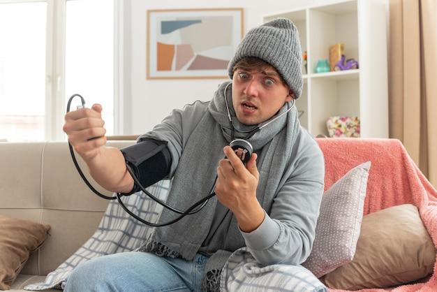 Angstige jonge zieke man met sjaal om nek met wintermuts gewikkeld in plaid die zijn druk meet met bloeddrukmeter zittend op de bank in de woonkamer