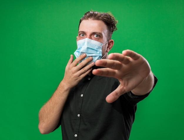 Angstige jonge, zieke slavische man met een medisch masker die zijn hand uitstrekt