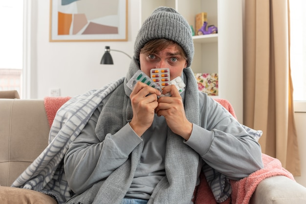Angstige jonge, zieke slavische man met sjaal om nek met een wintermuts met blisterverpakkingen voor medicijnen zittend op de bank in de woonkamer living