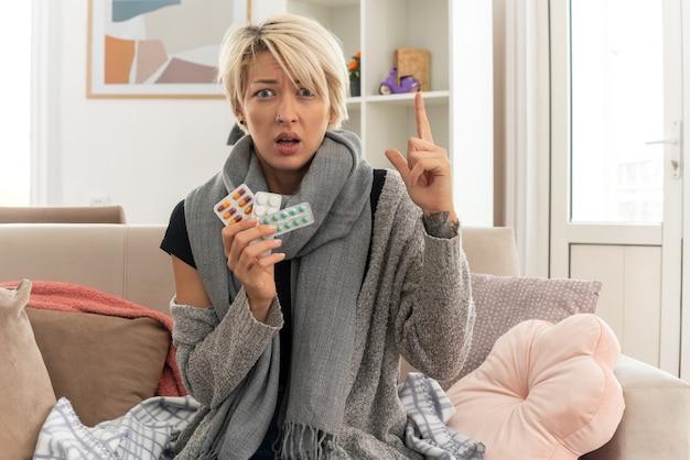 Angstige jonge zieke slavische vrouw met sjaal om haar nek die medicijnblisterverpakkingen vasthoudt en omhoog wijst terwijl ze op de bank in de woonkamer zit