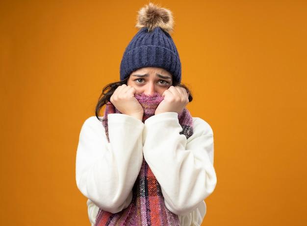 Angstige jonge zieke vrouw die de hoed en de sjaal van de gewaadwinter draagt die voorzijde behandelt die mond behandelt met sjaal die op oranje muur wordt geïsoleerd
