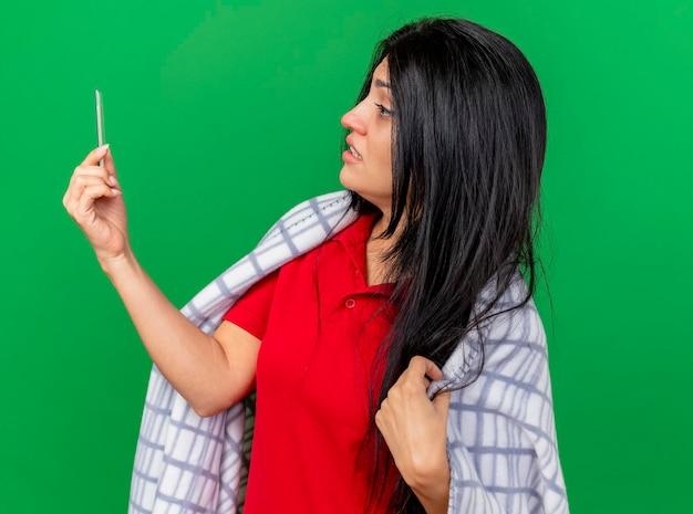 Angstige jonge zieke vrouw gewikkeld in geruite bedrijf en kijken naar thermometer grijpende plaid geïsoleerd op groene muur