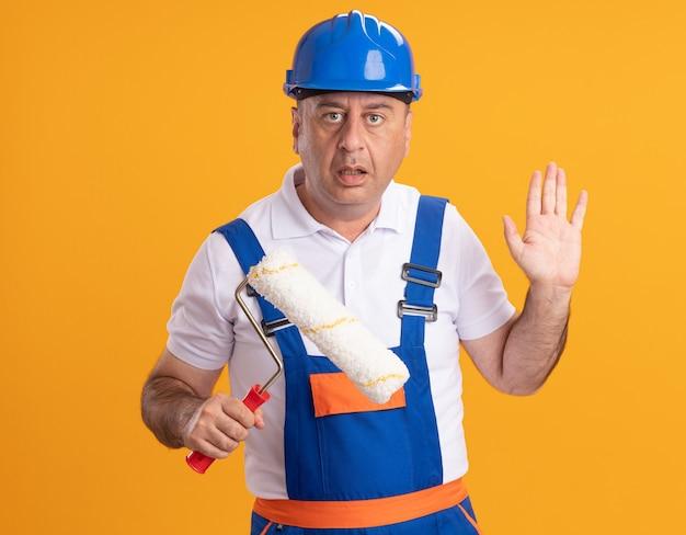 Angstige kaukasische volwassen bouwer man in uniform staat met opgeheven hand en houdt rolborstel op oranje