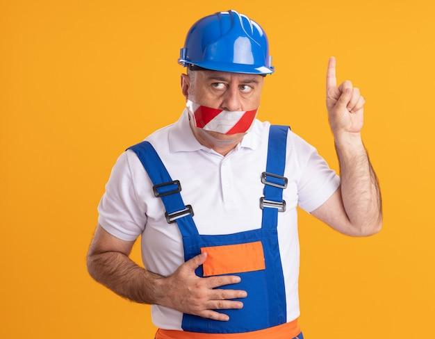 Angstige kaukasische volwassen bouwersmens in uniform behandelt mond met ducttape en wijst op sinaasappel