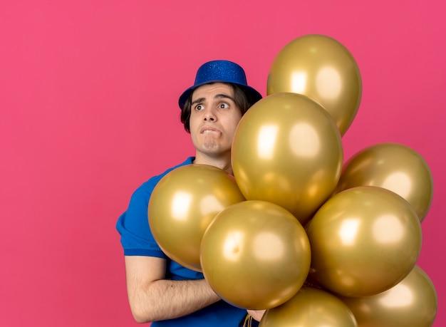 Angstige knappe blanke man met een blauwe feesthoed houdt heliumballonnen vast en kijkt naar de zijkant