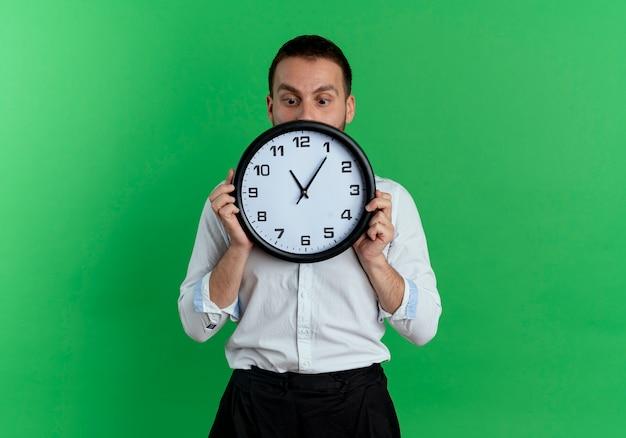 Angstige knappe man houdt en kijkt naar klok geïsoleerd op groene muur