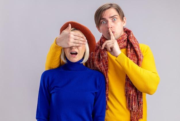 Angstige knappe slavische man met sjaal om zijn nek doet stiltegebaar en sluit de ogen van mooie blonde vrouw met baret op valentijnsdag Gratis Foto