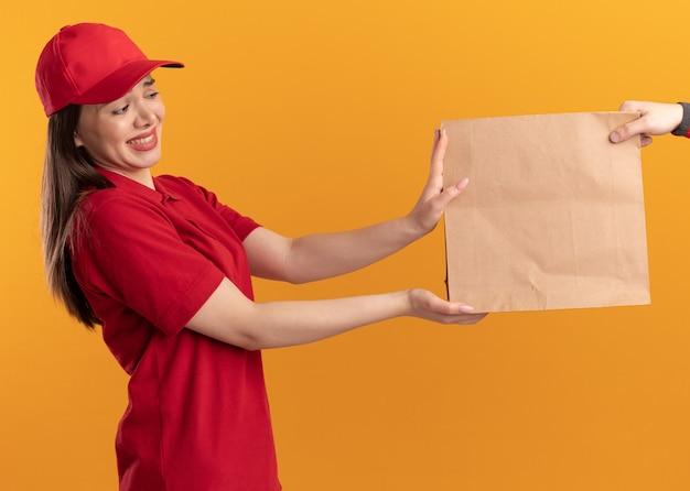 Angstige, mooie bezorger in uniform geeft iemand een papieren pakketje