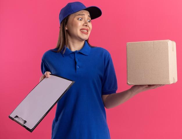 Angstige, mooie bezorger in uniform houdt klembord vast en kijkt naar cardbox