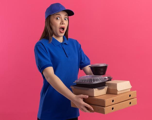 Angstige, mooie bezorger in uniform houdt voedselpakket en containers op pizzadozen geïsoleerd op roze muur met kopieerruimte