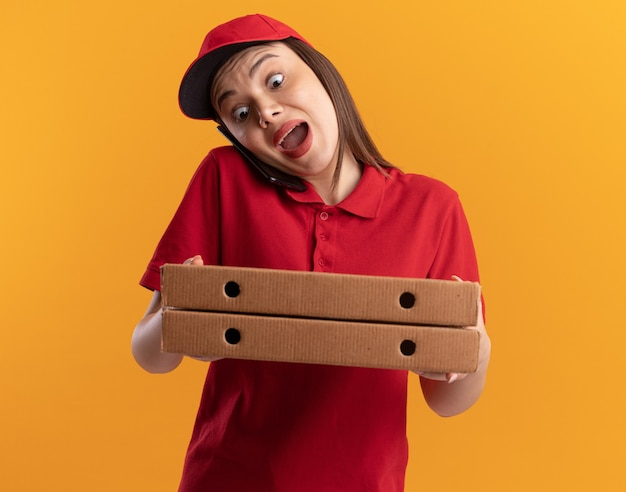 Angstige, mooie bezorger in uniform praat aan de telefoon en houdt pizzadozen vast