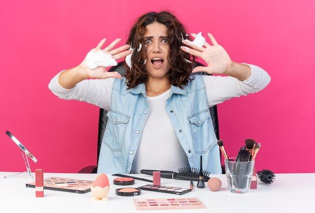 Angstige, mooie blanke vrouw die aan tafel zit met make-uphulpmiddelen die haarmousse aanbrengen en de handen open houden, geïsoleerd op een roze muur met kopieerruimte