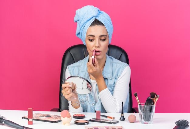 Angstige, mooie blanke vrouw met gewikkeld haar in een handdoek zittend aan tafel met make-uptools die naar een spiegel kijkt die lippenstift aanbrengt