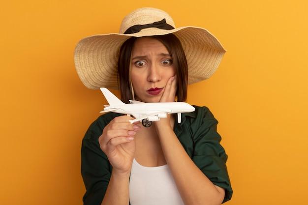 Angstige mooie blanke vrouw met strandhoed legt hand op gezicht en kijkt naar modelvliegtuig op oranje