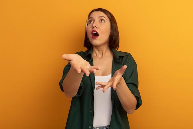 Angstige mooie blanke vrouw wijst naar de camera met twee handen die naar de zijkant kijken op oranje