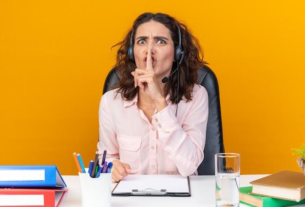 Angstige, mooie blanke vrouwelijke callcenter-operator op een koptelefoon die aan het bureau zit met kantoorhulpmiddelen die een stiltegebaar doen geïsoleerd op een oranje muur