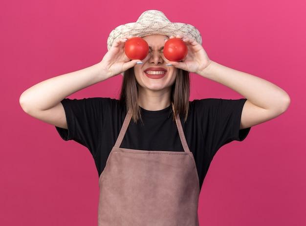 Angstige, mooie blanke vrouwelijke tuinman met een tuinhoed die tomaten voor de ogen houdt