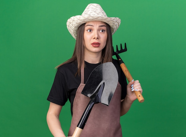 Angstige, mooie blanke vrouwelijke tuinman met een tuinhoed met hark en schop die naar de zijkant kijkt