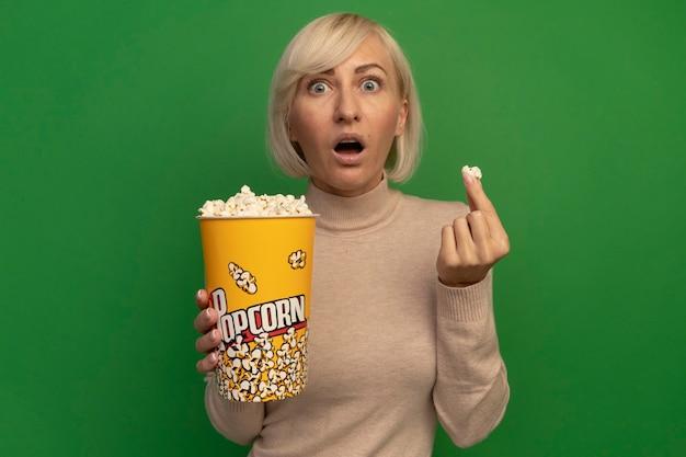 Angstige mooie blonde slavische vrouw houdt emmer popcorn op groen