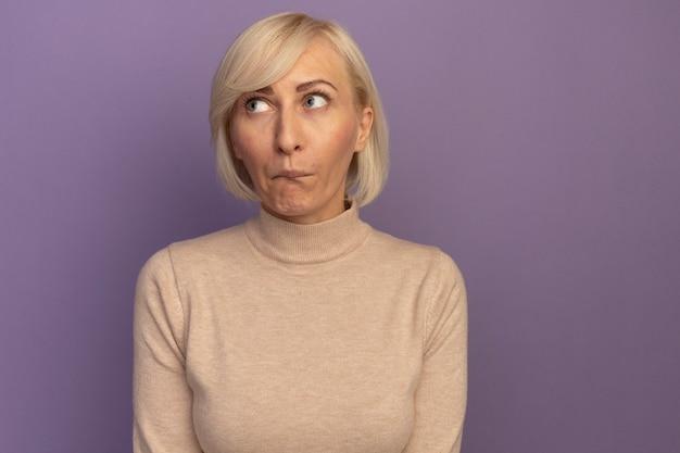 Angstige mooie blonde slavische vrouw kijkt naar de zijkant op paars