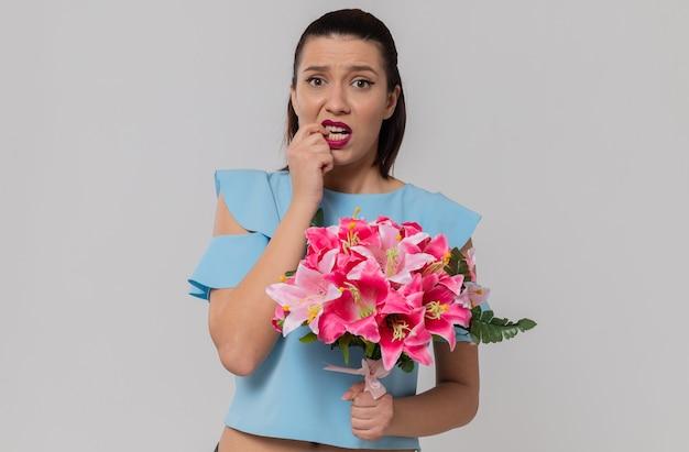 Angstige mooie jonge vrouw die een boeket bloemen vasthoudt en op haar nagel bijt