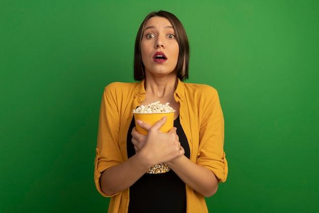 Angstige mooie vrouw houdt emmer popcorn geïsoleerd op groene muur