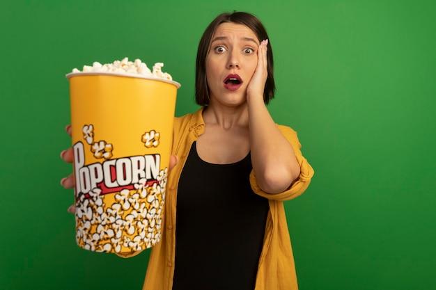 Angstige mooie vrouw legt hand op hoofd en houdt emmer popcorn geïsoleerd op groene muur
