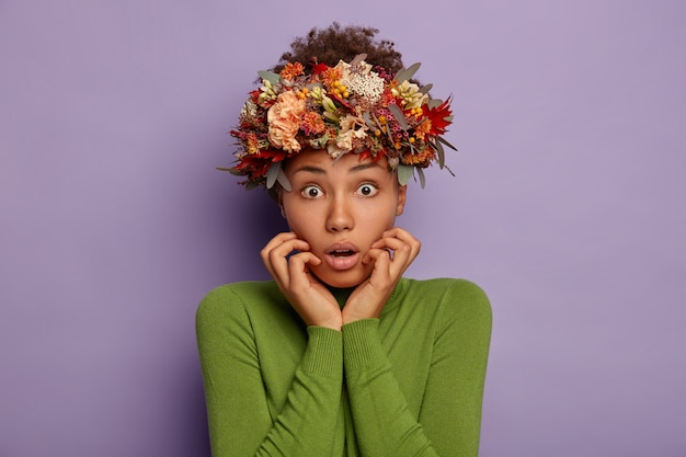 Angstige nerveuze vrouw met donkere huid, houdt handen in de buurt van geopende mond, kijkt geschokt naar de camera, draagt mooie krans gemaakt van herfstbladeren en bloemen, gekleed in casual groene poloneck