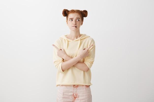 Angstige, onzekere roodharige meid die naar keuze kijkt, met de vingers zijwaarts wijzend