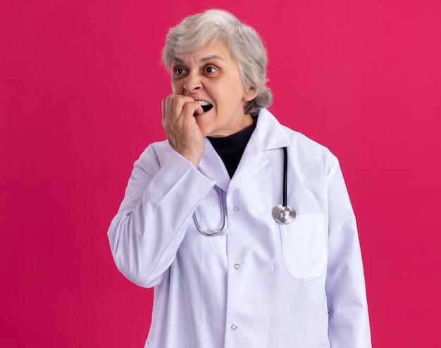 Angstige oudere vrouw in doktersuniform met stethoscoop die nagels bijt en naar de zijkant kijkt
